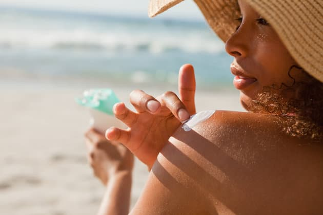 Young woman applying sunscreen on her shoulder while sitting on the beach